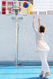 De donkerbruine vrouw werpt bal in mand Stock Fotografie