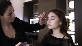 De donkerbruine vrouwelijke nake-omhooggaande kunstenaar met rode manicure maakt definitieve aanrakingen van oogschaduw op de oog stock footage