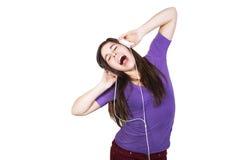De donkerbruine vrouwenglimlach en luistert muziek in haar hoofdtelefoons Stock Foto