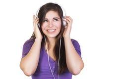De donkerbruine vrouwenglimlach en luistert muziek in haar hoofdtelefoons Stock Afbeeldingen