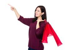 De donkerbruine vrouwengreep met het winkelen zak en de vinger benadrukken Royalty-vrije Stock Fotografie
