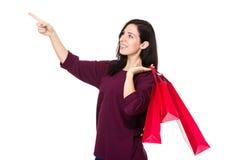 De donkerbruine vrouwenholding het winkelen zak en de vinger benadrukken Royalty-vrije Stock Afbeelding