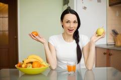 De donkerbruine vruchten die van de meisjesholding in de keuken zitten Royalty-vrije Stock Foto's