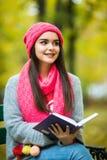 De donkerbruine zitting op de gevallen herfst gaat in een park, lezing een weg boek Stock Afbeeldingen