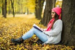 De donkerbruine zitting op de gevallen herfst gaat in een park, lezing een weg boek Royalty-vrije Stock Foto