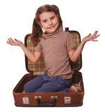 De donkerbruine zitting van het babymeisje in een koffer voor geïsoleerde reis Stock Afbeelding
