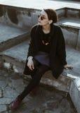 De donkerbruine zitting van het hipstermeisje in openlucht Stock Fotografie