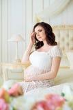 De donkerbruine zwangere jonge vrouw zit in een mooi binnenland met rozen Stock Afbeelding