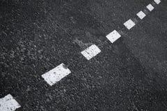 De donkere achtergrond van de asfaltweg met gestreepte lijn Stock Fotografie