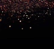 De donkere achtergrond van Defocused bokeh met gouden fee schittert en ma Stock Foto's