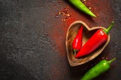 De donkere Achtergrond van het kruidvoedsel Rode en groene hete peper in een houten kom Stock Afbeeldingen