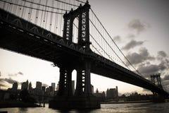 De donkere brug van Manhattan over de rivier en de stad in uitstekende stijl Royalty-vrije Stock Afbeelding