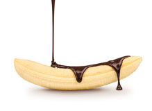 De donkere chocolade wordt gegoten op de rijpe banaan Stock Foto