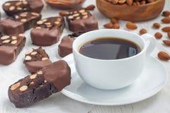 De donkere die koekjes van chocoladebiscotti met amandelen, met gesmolten chocolade worden behandeld, en horizontale kop van koff Royalty-vrije Stock Afbeelding