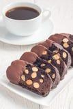 De donkere die koekjes van chocoladebiscotti met amandelen, met gesmolten chocolade worden behandeld, en verticale kop van koffie Royalty-vrije Stock Foto