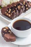 De donkere die koekjes van chocoladebiscotti met amandelen, met gesmolten chocolade worden behandeld, en verticale kop van koffie Royalty-vrije Stock Foto's