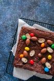 De donkere die vierkanten van de chocoladebrownie op een draadrek met cre wordt verfraaid Stock Afbeeldingen