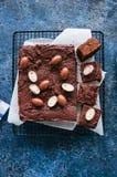 De donkere die vierkanten van de chocoladebrownie op een draadrek met cre wordt verfraaid Royalty-vrije Stock Foto