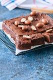 De donkere die vierkanten van de chocoladebrownie op een draadrek met cre wordt verfraaid Royalty-vrije Stock Fotografie