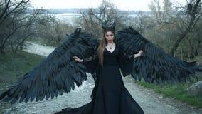 De donkere duivel kwam neer uit hemel, meisje met massieve zwarte vleugels en hoornen in lange uitstekende kleding met koele loss stock videobeelden