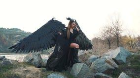 De donkere engel van dood met sterke zwarte veervleugels en hoornen kwam binnen neer uit hemel, voorbode van dood, meisje stock video