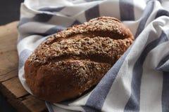 De donkere gehele verse korrel van het multigrainbrood gebakken op plattelander Stock Foto's
