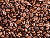 De donkere geroosterde achtergrond en de textuur van koffiebonen Stock Foto