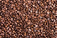 De donkere geroosterde achtergrond en de textuur van koffiebonen Stock Afbeeldingen