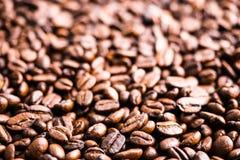 De donkere geroosterde achtergrond van koffiebonen en textuur, selectieve focu Royalty-vrije Stock Afbeeldingen