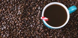 De donkere geroosterde achtergrond van koffiebonen met blauw gevulde koffiekop met pepermunt Stock Foto