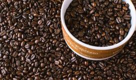 De donkere geroosterde die achtergrond van koffiebonen met mok met bonen wordt gevuld Royalty-vrije Stock Afbeelding