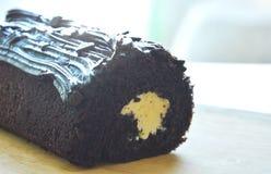 De donkere gevulde room van de chocoladecake broodje op houten hakkend blok Stock Foto's