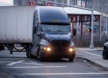 De donkere grote installatie Amerikaanse reusachtige semi vrachtwagen met aanhangwagen zet kruis aan Royalty-vrije Stock Foto