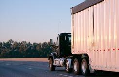 De donkere grote installatie semi vrachtwagen met dagcabine draagt reusachtige bulkaanhangwagenlooppas Royalty-vrije Stock Fotografie