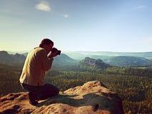 De donkere haarmens neemt foto door grote spiegelcamera op de hals op de piek van berg bij zonsopgang Stock Fotografie