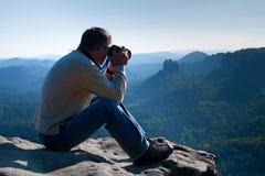 De donkere haarmens neemt foto door grote spiegelcamera op de hals op de piek van berg bij zonsopgang Royalty-vrije Stock Foto