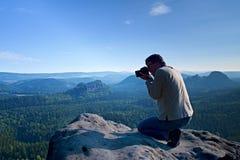 De donkere haarmens neemt foto door grote spiegelcamera op de hals op de piek van berg bij zonsopgang Royalty-vrije Stock Afbeelding