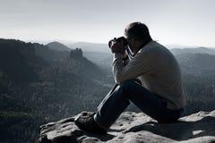 De donkere haarmens neemt foto door grote spiegelcamera op de hals op de piek van berg bij zonsopgang Stock Afbeelding
