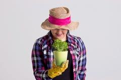 De donkere Haarvrouw in Tuinuitrusting houdt een Vers Kruid Stock Foto