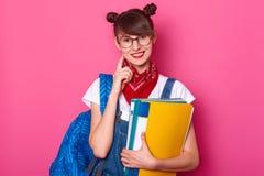 De donkere haired student met blauwe zak, houdt kleurrijke document omslag, glimlachen, houdt voorvinger op haar wang Het jonge m royalty-vrije stock foto's