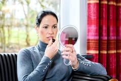 De donkere haired vrouw die thuis maakt omhoog inschrijven Royalty-vrije Stock Fotografie