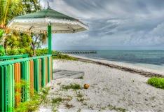 De donkere hemel van het wolkenpatroon over tropische strand en kiosk Royalty-vrije Stock Afbeeldingen