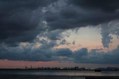 De donkere hemel van de regenwolk op overzees de stadszeehaven Stock Afbeeldingen