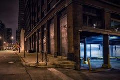 De donkere hoek van de binnenstad van de stadsstraat bij nacht stock foto