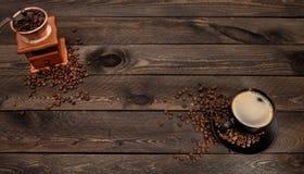 De donkere houten textuur met een kop van koffie en koffiemolen Royalty-vrije Stock Foto's