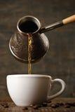 De donkere koffie giet van een koper cezve in een witte kop Stock Afbeeldingen