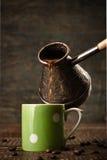 De donkere koffie giet van een koper jezve in een groene ceramische vinta Royalty-vrije Stock Afbeelding