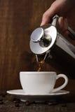 De donkere koffie giet van een koper jezve in een witte kop Royalty-vrije Stock Foto's