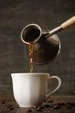 De donkere koffie giet van een koper jezve in een witte kop Royalty-vrije Stock Foto