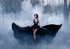 De donkere koningin, met naakte lange benen, loopt mist Een luxueuze zwarte kleding flakkert in verschillende richtingen, zoals d Stock Foto